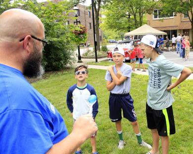Community Relations Committee member Troy O'Quinn, left, explains the rules of the egg and spoon race to competitors.