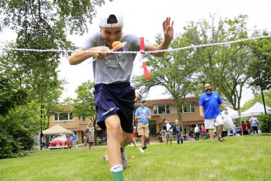 Jack Van Etten crosses the finish line for a victory in an egg and spoon race.