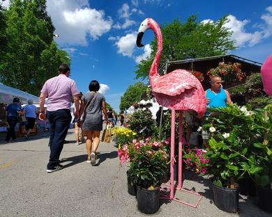 A large flamingo yard sculpture presides over the flow of Artisan Street Fair patrons. (EC)