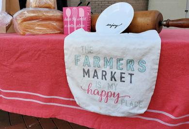 """A sign at Amy Crump's Bite Me Bakery booth sums up the feelings of many market patrons: """"The farmers market is my happy place."""" (EC)"""