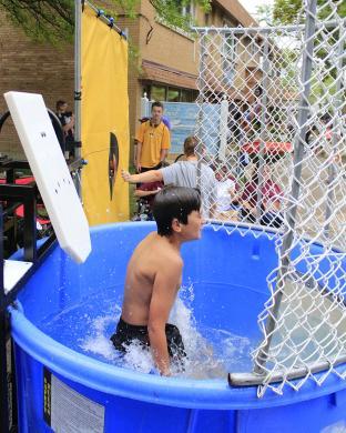 Logan Sesol drops into the water at the St. Joseph Athletic Association dunk tank. (EC)