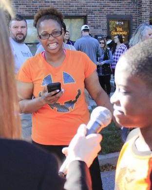 Delilah Butler watches her son, Jermaine, do an interview before the race. Jermaine expressed confidence in his chances to win, noting that he had run 10 miles to prepare.