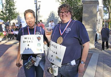 "Susan Gates, left, and Ginny Williamson sport ""Will drink 4 art"" signs, plus tokens of each event sponsor."