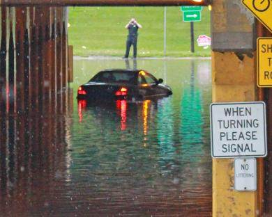 A car is stalled in the westbound lane of the Dixie Highway viaduct after heavy rains in August 2014. Before mutual aid agreements became common, Homewood firefighters used to park a truck on the west side of the viaduct when heavy rain was expected so the west side of town would still have service. (Chronicle file photo)