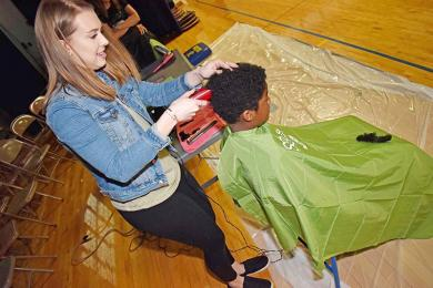 """Stylist Kimmie Major from Artistix Salon in Homewood makes the first cut on Xavier White, a student at Parker Junior High School. Xavier raised more than $1,700 dollars for St. Balderick's Foundation during the event.  """"I wanted to do this after I saw a video with a kid who has cancer,"""" said Xavier. """"Today, I'm making a difference."""""""