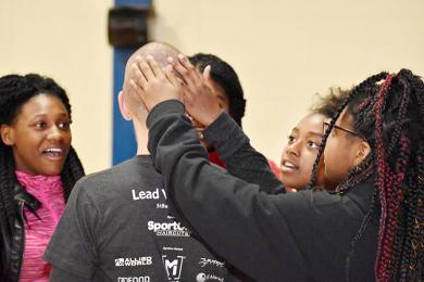 Parker Junior High students, from left, Jamie Kohn, Iyanna Dixon, Kaylee Richmond and Zaria Williams check out the bald head of Cindy Hayes, who works at the school and organized Parker's first St. Balderick's Day event.