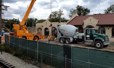 Crews pour concrete on Saturday on the east side of the Homewood train station building.