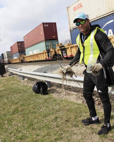 Camson Addenuga helps clean up the area between Harwood Avenue and the railroad tracks in downtown Homewood during Community Cleanup Day.