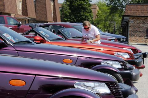 Debbie Cothran polishes a Plymouth Prowler, one of five from the collection of the late Ed Wasik of Glenwood, that was on display at St. Paul Community Church in Homewood on June 16 during the annual Drivin' the Dixie tour.