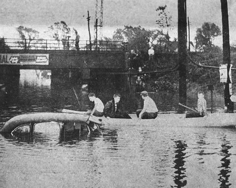 """The caption on this photo from the Oct. 12, 1954, Homewood-Flossmoor Star reads: """"Aftermath of torrential rains which flooded Homewood area over week-end are pictured in the above photographs. In upper left, boys take advantage of the once-in-a-lifetime opportunity to go boating in the village as they paddle past stalled and nearly submerged car at Dixie highway viaduct."""" Viaduct flooding certainly isn't new. (From the Homewood Historical Society archives)"""
