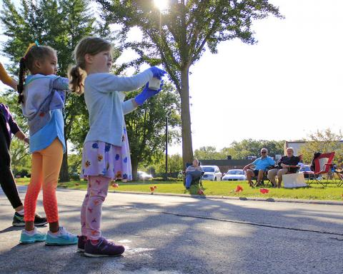 Chandler Jarrell, left, and Erin Graves, students at Flossmoor Montessori School, offer cups of water to runners near Heather Hill School.